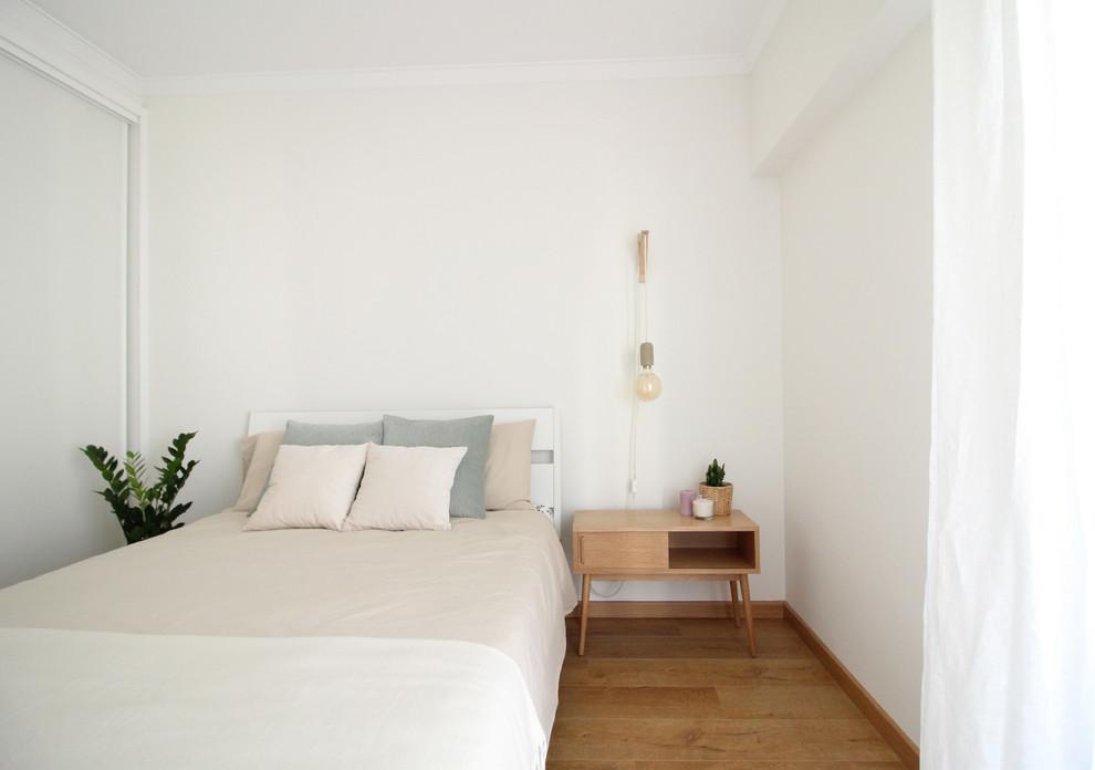 Danish guest medium tone wood floor and brown floor bedroom photo in Other with white walls