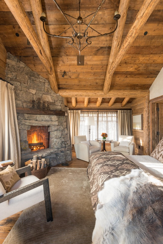 Example of a mountain style medium tone wood floor bedroom design in Other with beige walls, a corner fireplace and a stone fireplace