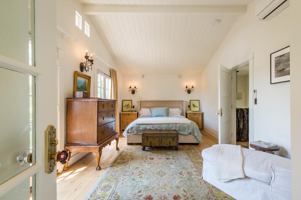 Example of a country master light wood floor and beige floor bedroom design in Los Angeles with beige walls