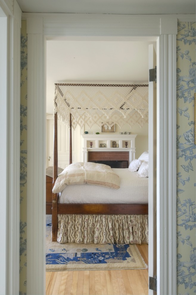 Elegant light wood floor bedroom photo in Portland Maine with beige walls and a standard fireplace
