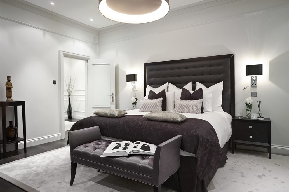 Example of a transitional dark wood floor bedroom design in London with white walls