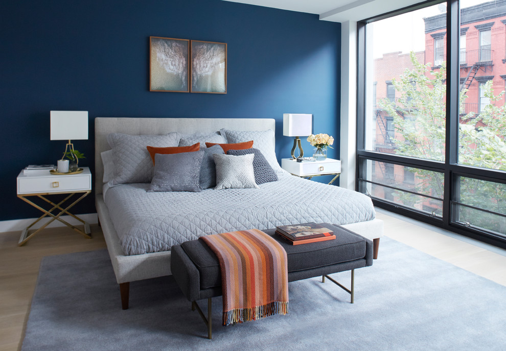 Example of a mid-sized trendy guest light wood floor and beige floor bedroom design in Other with blue walls and no fireplace