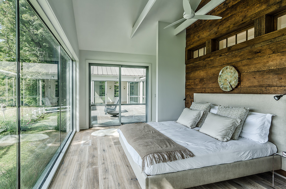 Mid-sized farmhouse light wood floor bedroom photo in New York with white walls