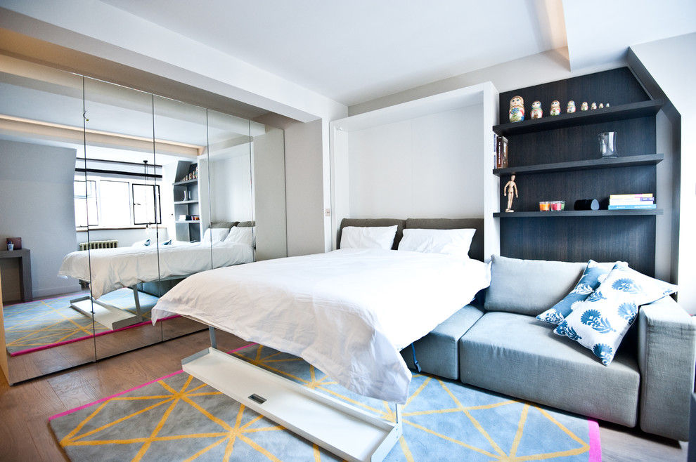 Small trendy master medium tone wood floor bedroom photo in London with gray walls and no fireplace