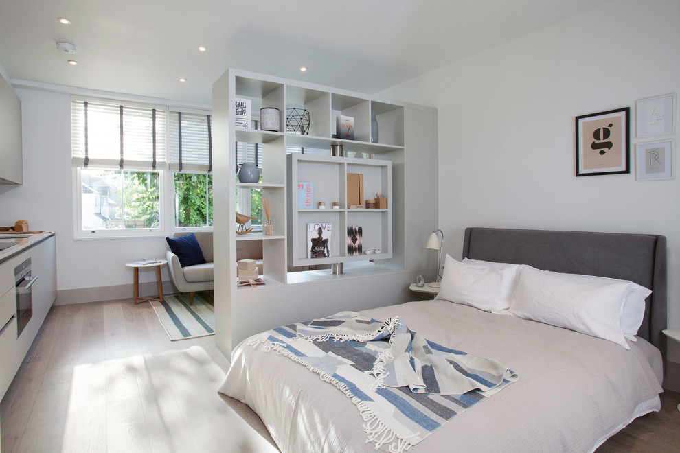 Inspiration for a scandinavian bedroom in London with white walls and light hardwood floors.