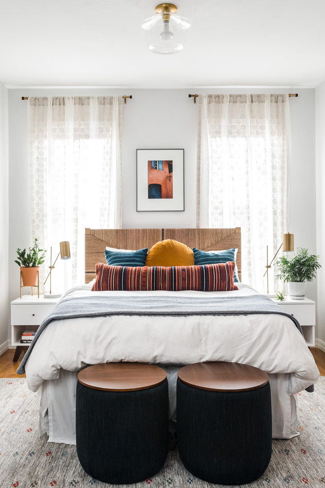 Inspiration for a tropical medium tone wood floor and brown floor bedroom remodel in Boston with white walls