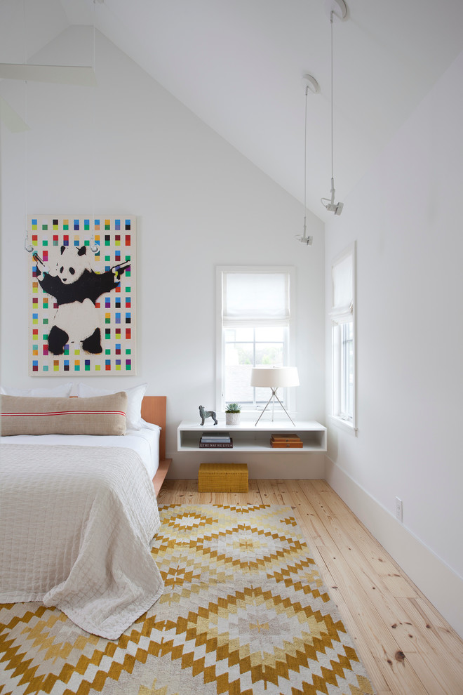 Example of a danish master light wood floor bedroom design in Austin with no fireplace and white walls