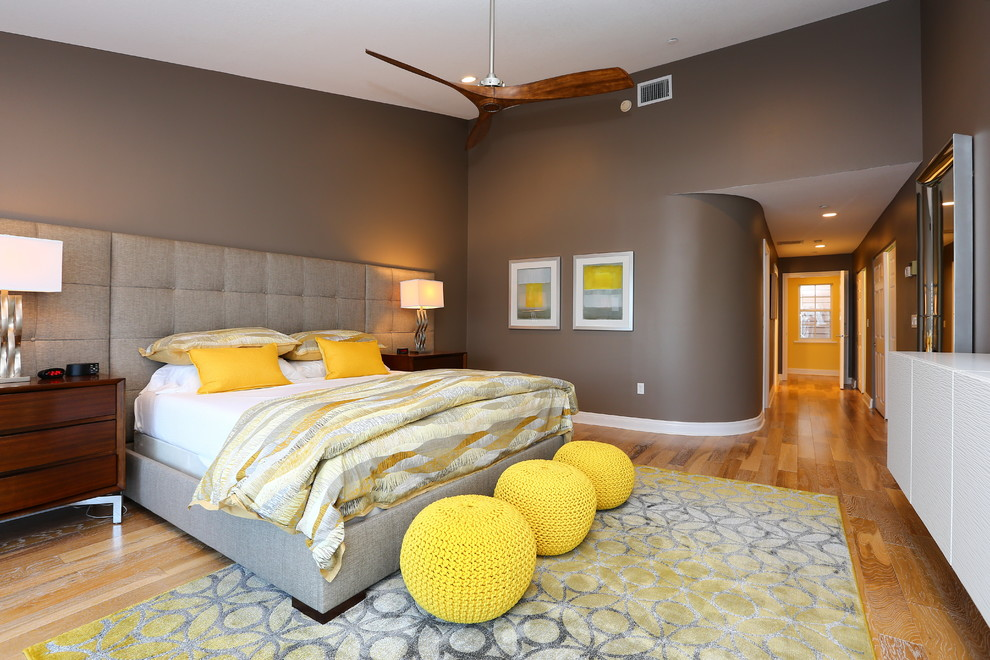 Inspiration for a contemporary medium tone wood floor and yellow floor bedroom remodel in Tampa with brown walls