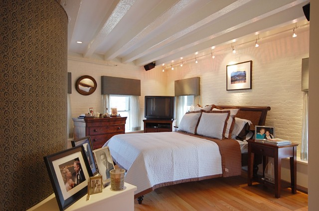 midsized trendy master medium tone wood floor bedroom photo in boston with beige walls