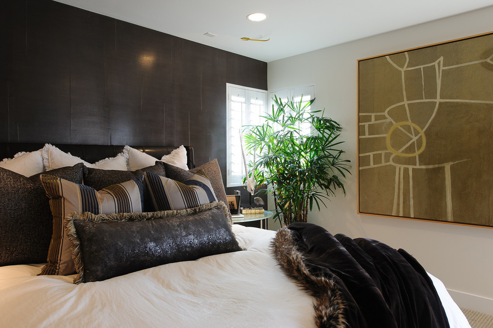 Example of a trendy carpeted bedroom design in Los Angeles with black walls and no fireplace