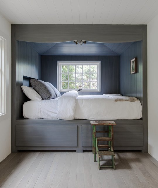 Example of a mid-sized coastal guest medium tone wood floor and brown floor bedroom design in Santa Barbara with white walls
