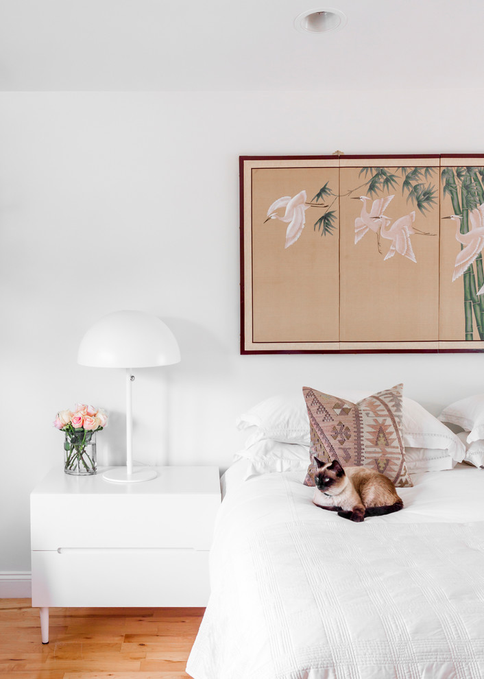 Example of a transitional medium tone wood floor and brown floor bedroom design in Boston with white walls