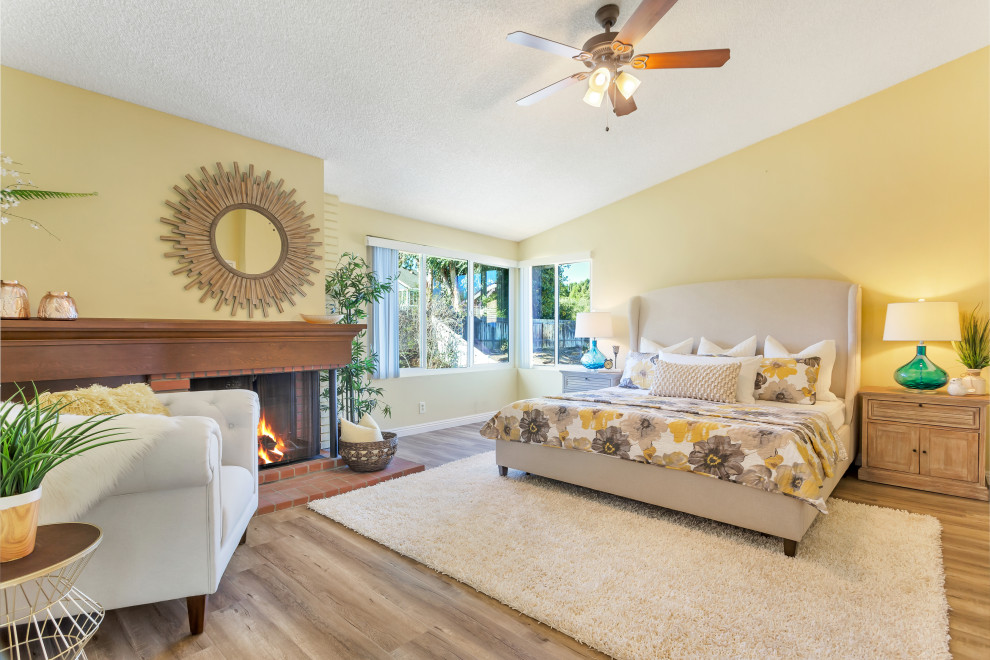 Inspiration for a transitional medium tone wood floor and brown floor bedroom remodel in Los Angeles with yellow walls and a standard fireplace