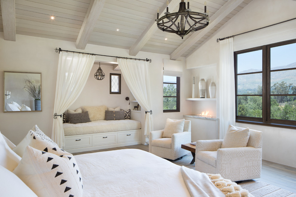Large tuscan master light wood floor and brown floor bedroom photo in Santa Barbara with white walls and a ribbon fireplace