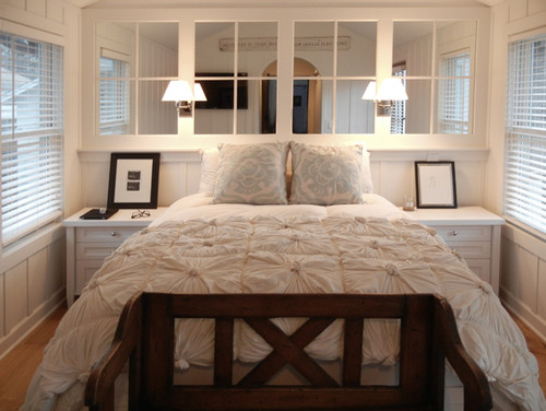 Small bedroom with mirrors to make it look bigger behind the bed on the wall