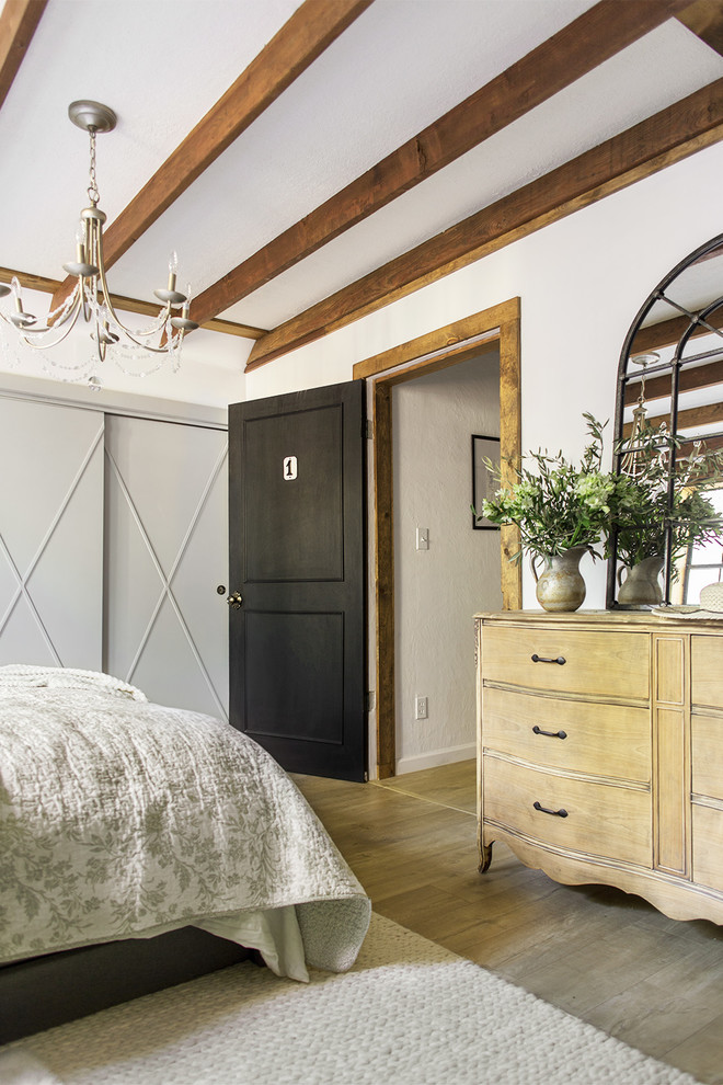 Bedroom - mid-sized rustic master laminate floor and brown floor bedroom idea in Tampa with white walls
