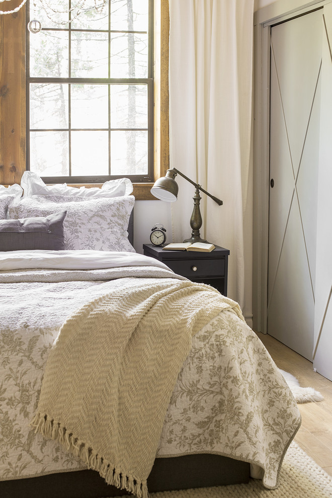 Example of a mid-sized mountain style master laminate floor and brown floor bedroom design in Tampa with white walls