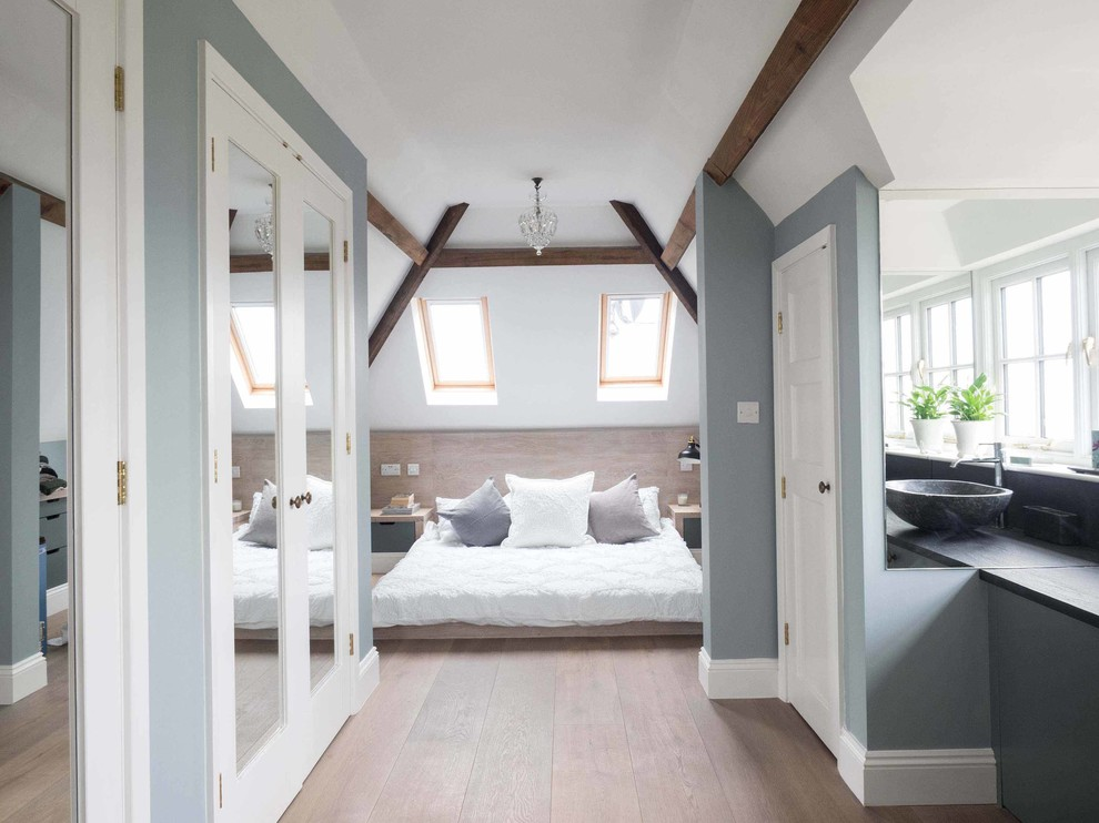 Example of a mid-sized cottage guest light wood floor bedroom design in Gloucestershire with blue walls