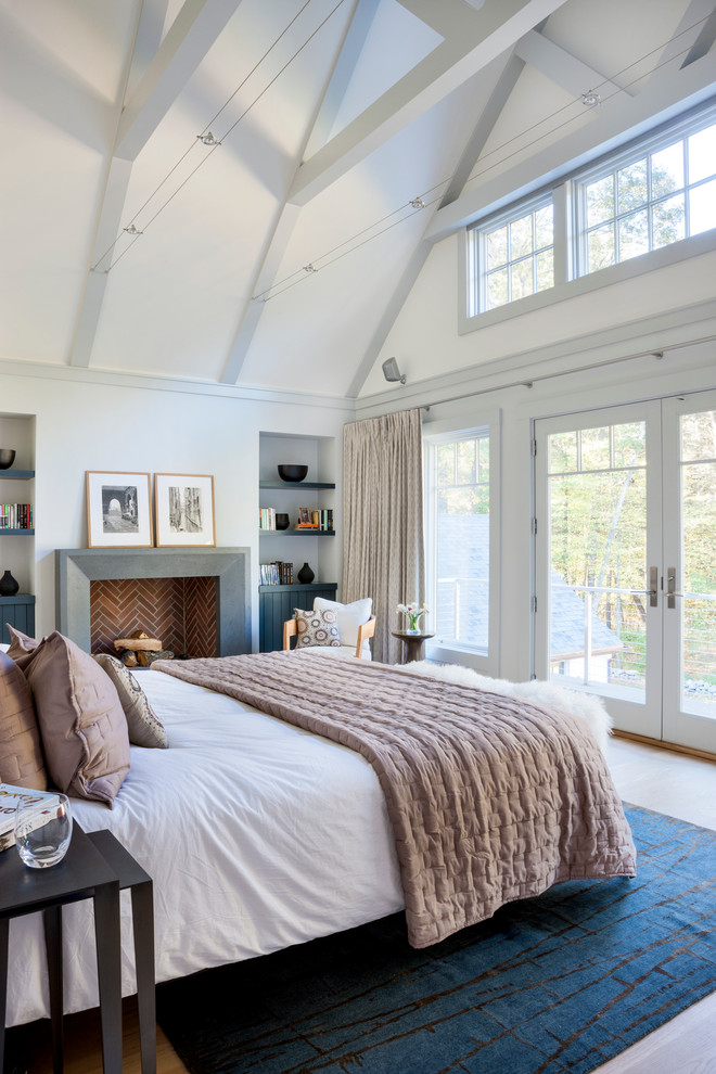 Inspiration for a beach style light wood floor bedroom remodel in Boston with white walls and a standard fireplace
