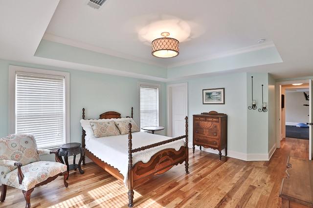 Imagen de habitación de invitados tradicional, de tamaño medio, sin chimenea, con paredes azules y suelo de madera en tonos medios