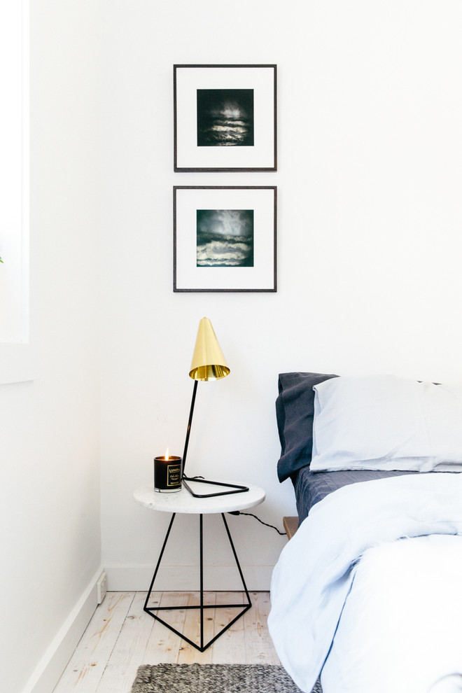 Example of a small danish guest painted wood floor bedroom design in Sydney with white walls