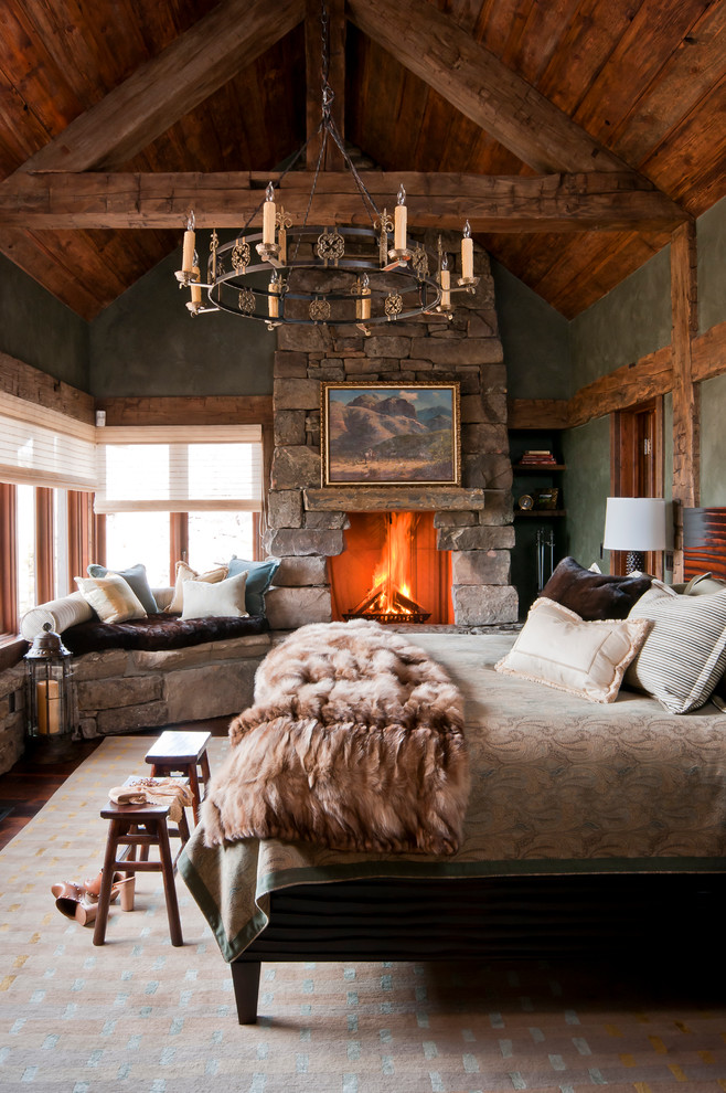 Mountain style guest carpeted bedroom photo in Other with a standard fireplace, a stone fireplace and green walls