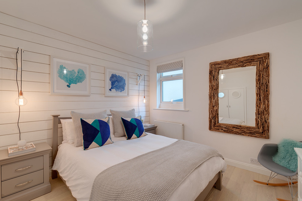 Example of a coastal light wood floor bedroom design in Devon with white walls