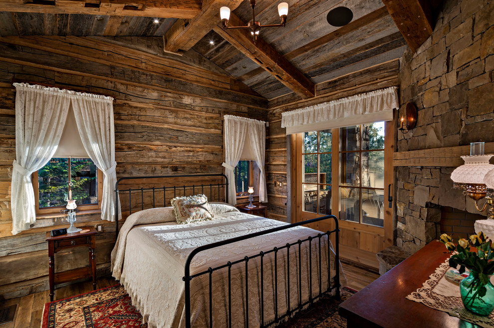 Example of a mountain style master dark wood floor bedroom design in Other with brown walls, a corner fireplace and a stone fireplace