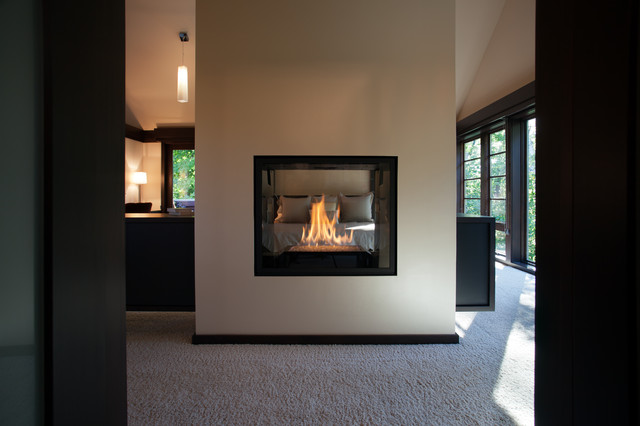 double sided fireplace in master suite modern bedroom