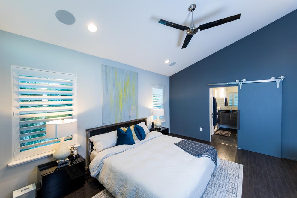 Example of a mid-sized trendy master dark wood floor and brown floor bedroom design in Jacksonville with blue walls