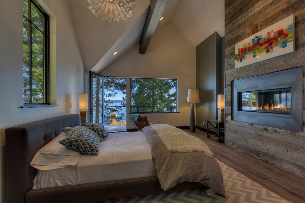 Trendy dark wood floor bedroom photo in San Francisco with beige walls, a ribbon fireplace and a metal fireplace