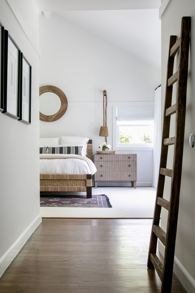 Example of a huge transitional master medium tone wood floor and brown floor bedroom design in New York with white walls