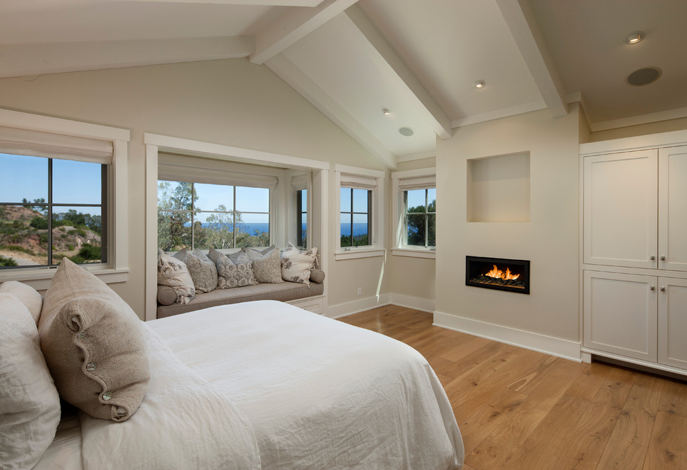 Bedroom - large traditional master medium tone wood floor bedroom idea in Santa Barbara with a ribbon fireplace, beige walls and a plaster fireplace
