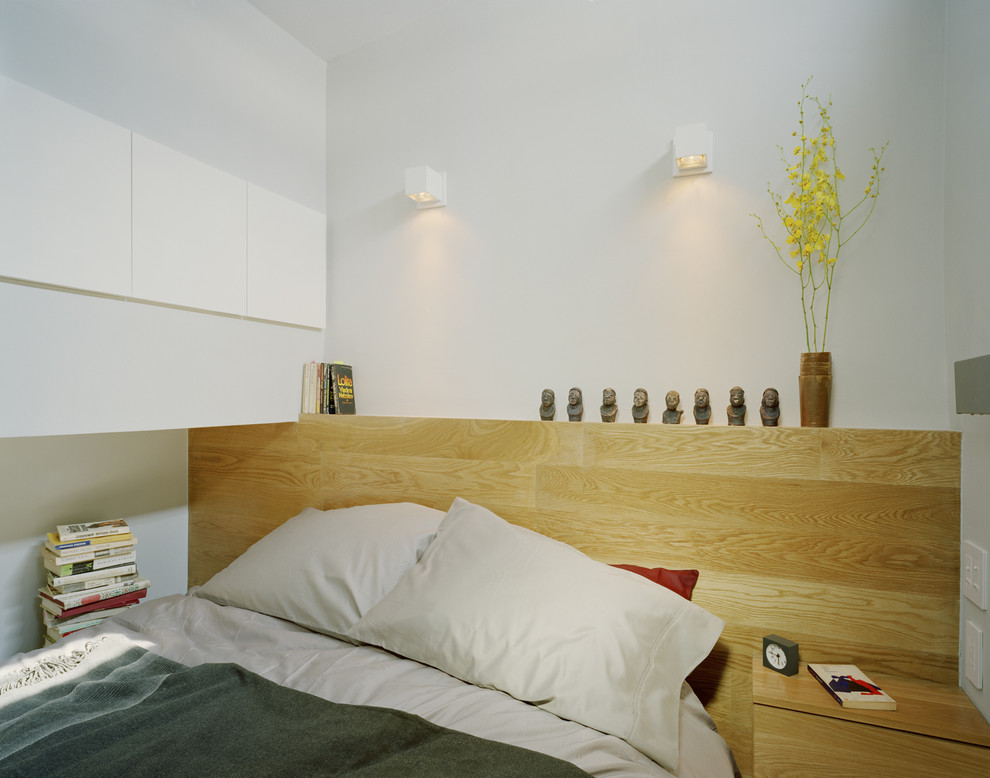 Example of a minimalist bedroom design in New York with white walls
