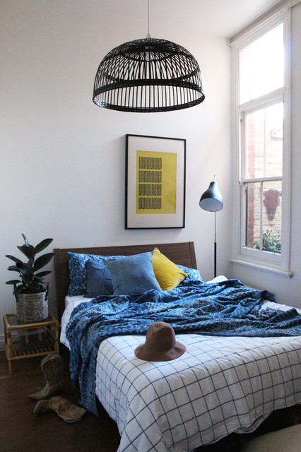 Example of an eclectic guest light wood floor bedroom design in Melbourne with white walls