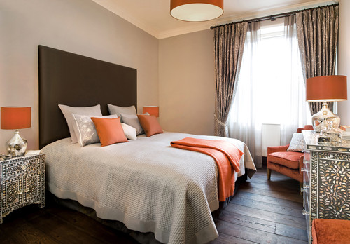 Tan-walled bedroom with orange pillows, throw, lampshades, and seat