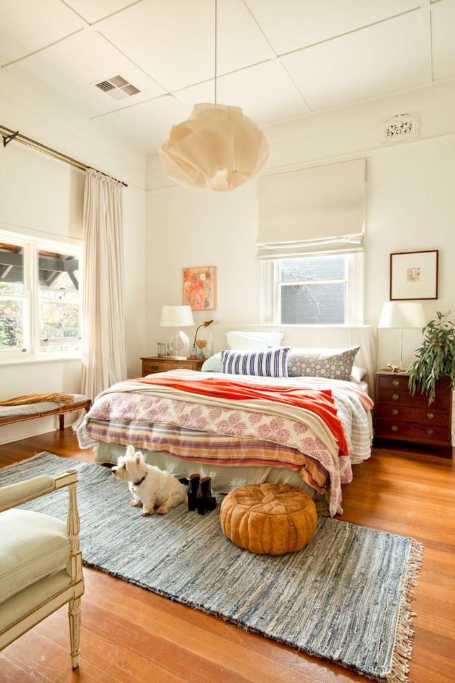 Eclectic medium tone wood floor and orange floor bedroom photo in Perth with white walls