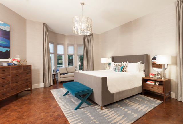 Example of a mid-sized transitional master medium tone wood floor and orange floor bedroom design in Austin with beige walls