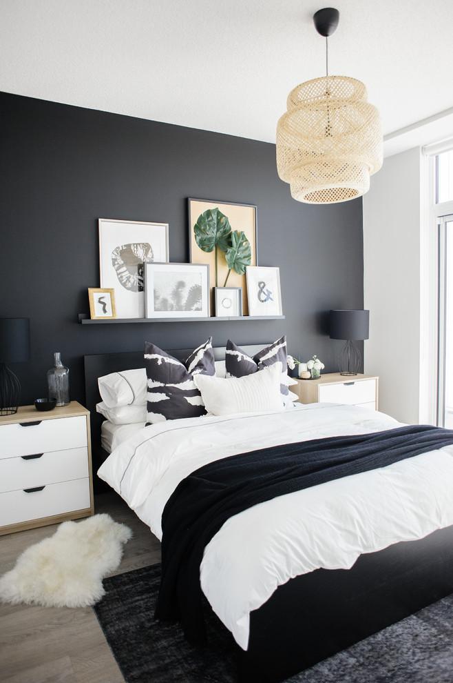 Example of a trendy light wood floor and beige floor bedroom design in Toronto with black walls