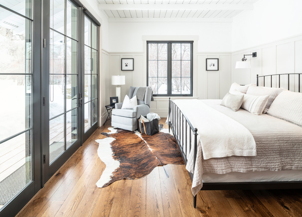 Inspiration for a country dark wood floor and brown floor bedroom remodel in Salt Lake City with white walls