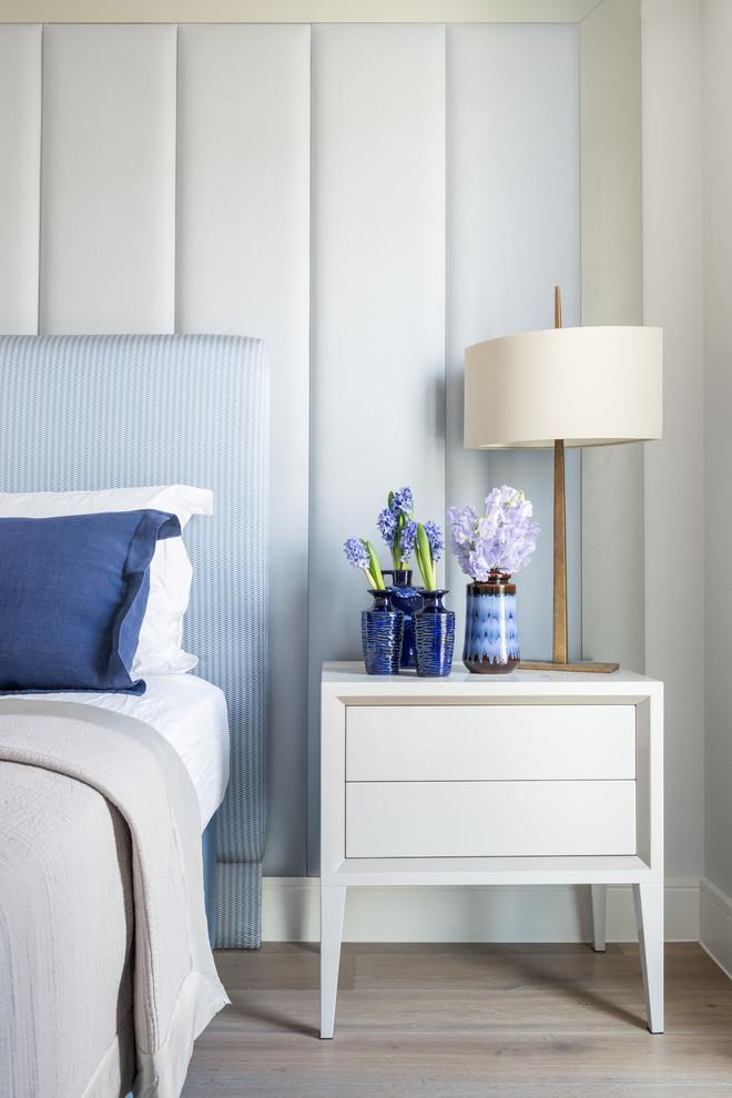 Trendy medium tone wood floor bedroom photo in London with blue walls