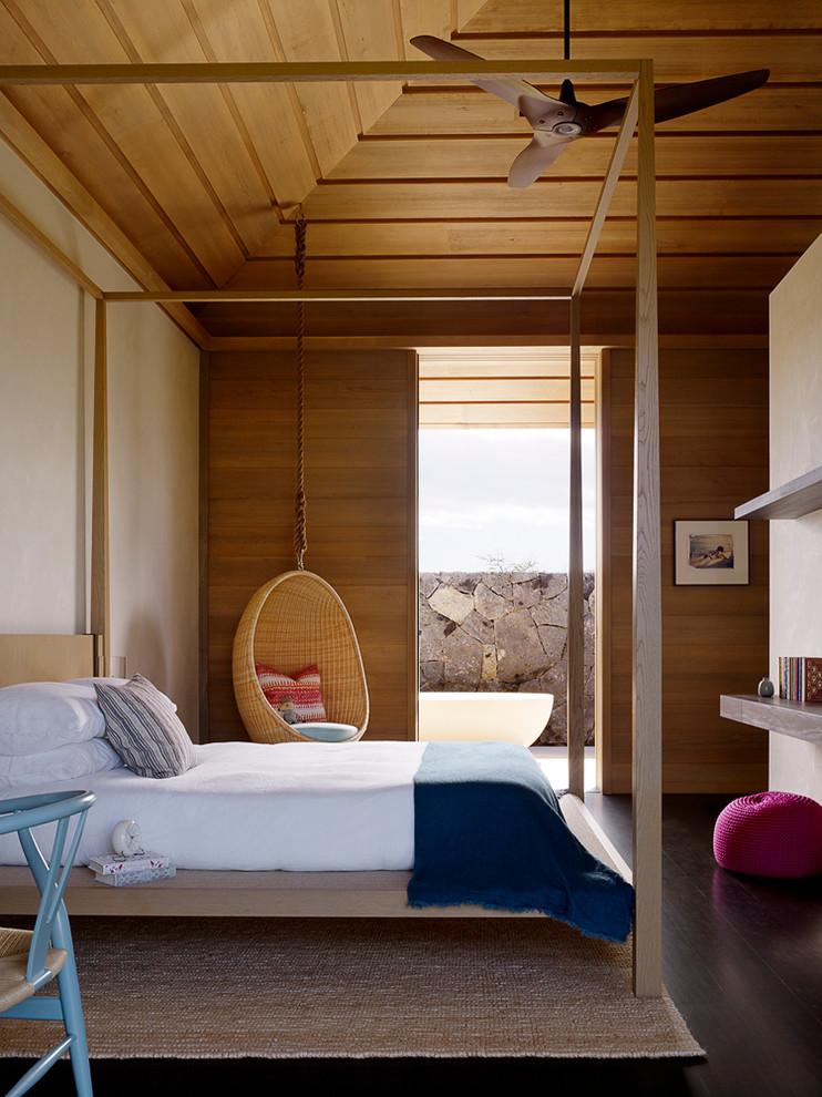 Trendy dark wood floor bedroom photo in Hawaii with beige walls