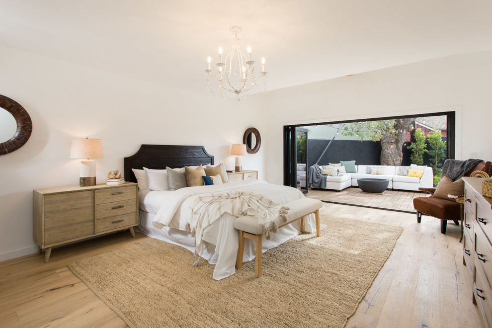 Farmhouse master light wood floor bedroom photo in Los Angeles with white walls and no fireplace