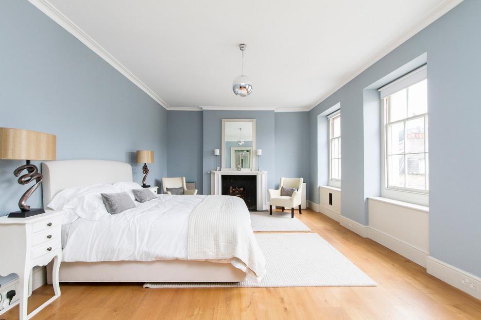 Bedroom - transitional medium tone wood floor bedroom idea in London with blue walls