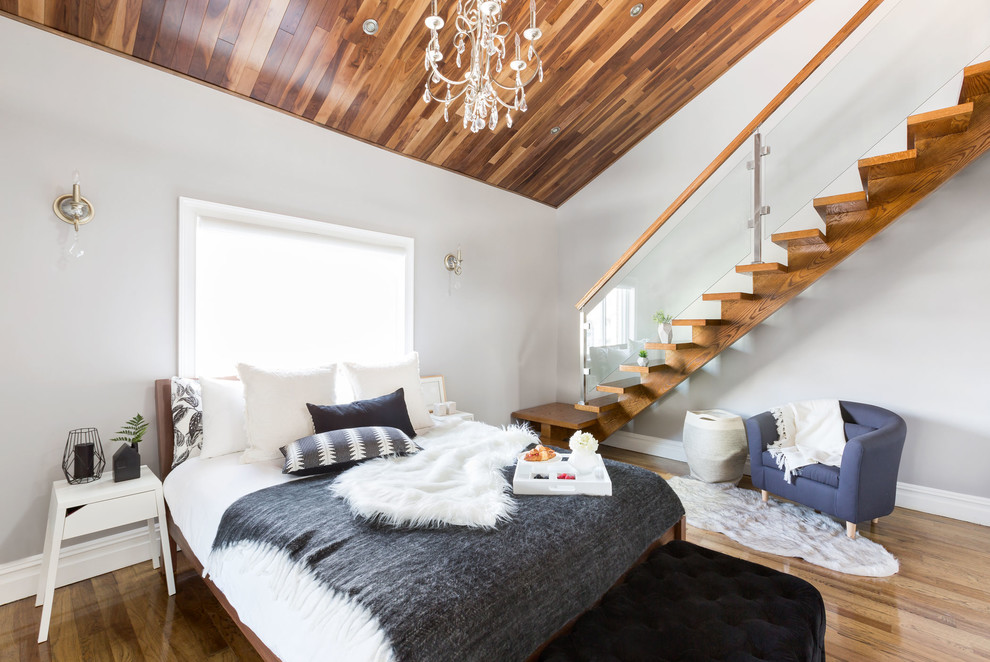 Example of a trendy master medium tone wood floor bedroom design in New York with white walls and no fireplace