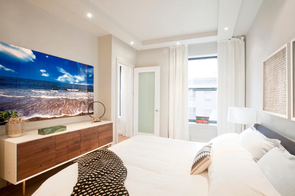 Trendy medium tone wood floor bedroom photo in New York with beige walls
