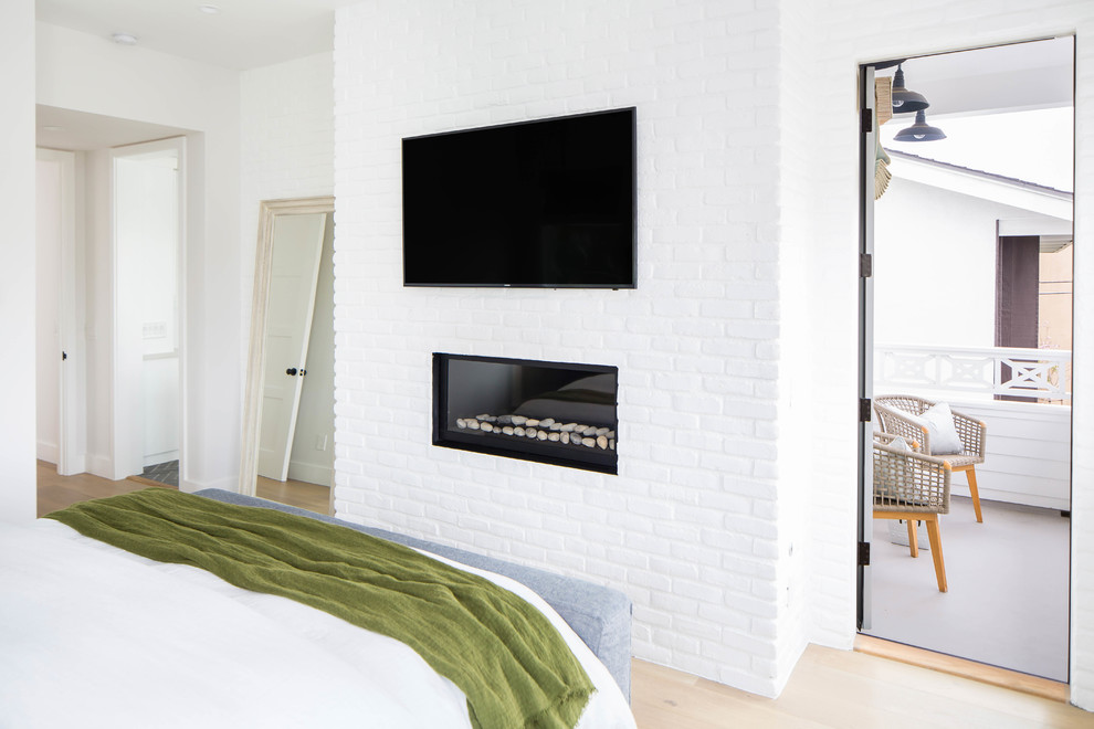 Mid-sized farmhouse master medium tone wood floor and beige floor bedroom photo in Orange County with white walls, a standard fireplace and a brick fireplace