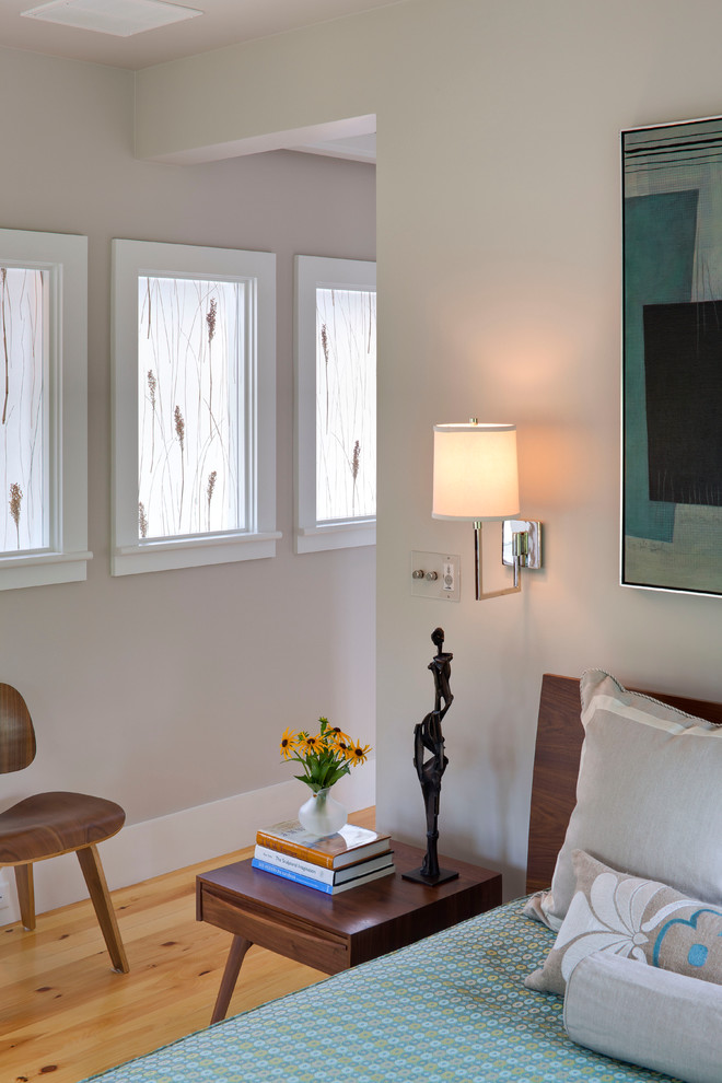 Inspiration for a mid-sized contemporary guest light wood floor and brown floor bedroom remodel in Boston with white walls and no fireplace