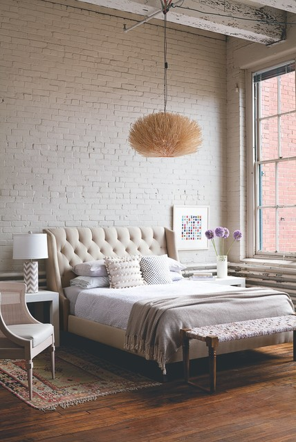 Inspiration for a mid-sized industrial master bedroom in Boston with white walls, medium hardwood floors, no fireplace and brown floor.
