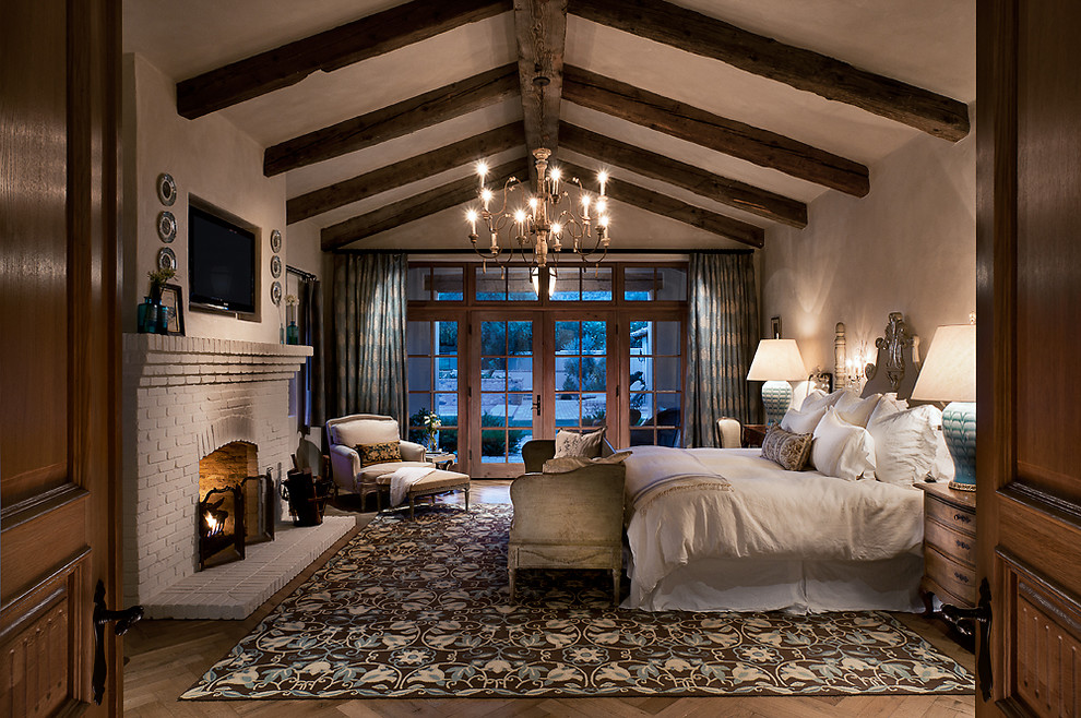 Example of a tuscan medium tone wood floor bedroom design in Phoenix with a standard fireplace, a brick fireplace and gray walls